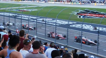 IndyCars on the front straight of the Texas Motor Speedway, racing by at speed...