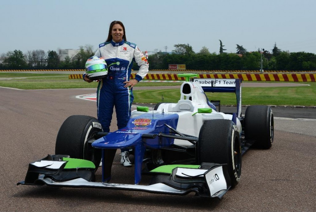 Simona De Silvestro beside Formula1 test car at Ferrari's Fiorano Circuit, April 2014